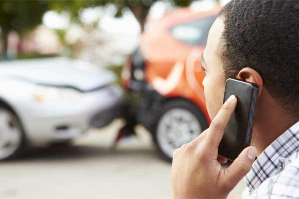 A man calling emergency services after a car accident.