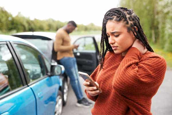 A woman on her phone after a car accident